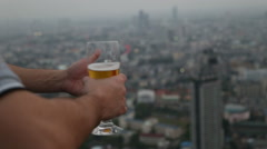 Man hand holding mug of beer in sky deck pub Stock Footage