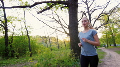 Beautiful woman in T-shirt makes a run in the spring forest Stock Footage