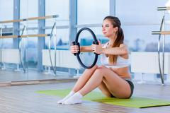 Pilates woman magic ring exercise workout at gym indoor - stock photo