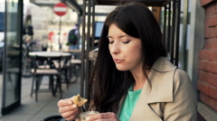 Young woman talking and dipping bread in sauce sitting in cafe Stock Footage