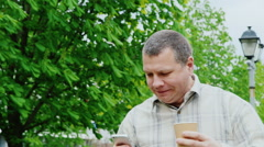 Life in a hurry. A man very quickly goes down the street, drinking coffee on the Stock Footage