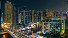 Dubai Marina at night timelapse with light trails of boats on the water and cars Stock Footage