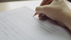 Student filling out answers to a test with a pencil Stock Footage