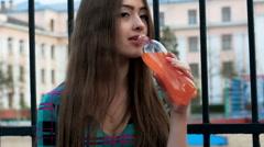 Young beautiful woman drinking orange soda Stock Footage