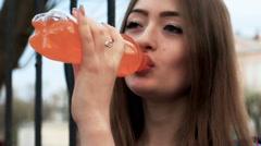 Beautiful woman drinking orange soda. Close up Stock Footage
