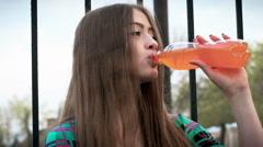 Beautiful woman drinking orange soda. Slow motion Stock Footage