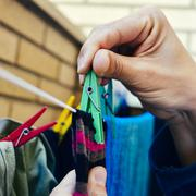 young man hanging up the clothes - stock photo