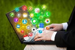 Hand pressing modern laptop with mobile app icons and symbols - stock photo