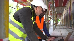 Construction workers with safety jacket and helmet at computer. Tracking shot Stock Footage