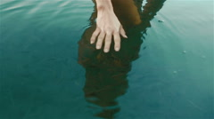 Beautiful manicured woman hands close up in the clean blue water with herd of - stock footage