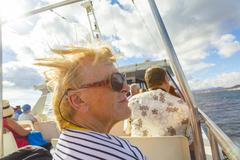 happy elderly woman enjoys the boat trip - stock photo