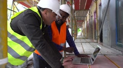 Engineers with safety jacket and helmet at computer. Tracking shot - stock footage