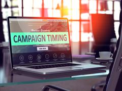 Campaign Timing on Laptop in Modern Workplace Background - stock illustration