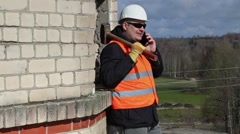 Construction worker with sledgehammer talking on smart phone Stock Footage