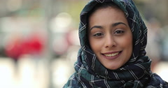 Young woman wearing hijab in city serious to smiling face portrait - stock footage