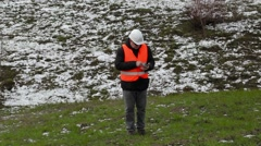 Civil engineer walking up to hill and using tablet PC Stock Footage