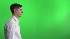 Young businessman lunges forwards searching binoculars on greenscreen Stock Footage