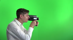 Young businessman with funny face making a movie with old film movie camera Stock Footage