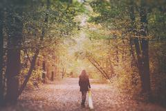 Sad woman walking alone in the woods - stock photo