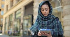Young woman wearing hijab in city using tablet computer Stock Footage