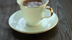 Hot tea in a porcelain cup on the saucer Stock Footage