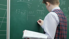 Close up of schoolboy of primary school solves math on the blackboard, 4k shot - stock footage