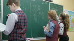 Pupils of primary school solving math on the blackboard, 4k shot - stock footage