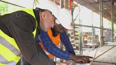 Side view: two engineers at computer on construction site among scaffolding - stock footage