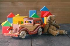 House made of wooden blocks to assemble, near atoy and a wooden toy car Stock Photos
