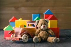 House made of wooden blocks to assemble, near atoy and a wooden toy car - stock photo