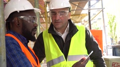 Engineer providing instructions to a colleague with orange vest and tablet - stock footage