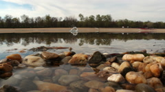 Stones thrown into water - stock footage