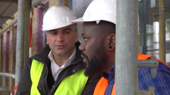 Engineers discussing and sitting among scaffolding - stock footage