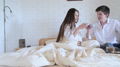 Couple drinking tea in bed in the loft room Stock Footage