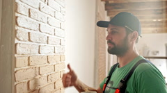 Renovation: man painting a wall, enjoying the work. Slow motion - stock footage