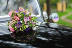 Bouquet of flowers on hood retro wedding car - stock photo