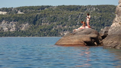 Girls sunbathing on a rock at the lake on a sunny summer day Stock Footage