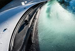 Frozen car windshield and wipers and hood. Stock Photos