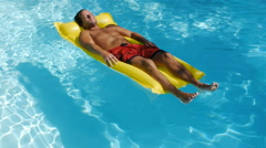 Man on swimming pool raft floating on water Stock Footage