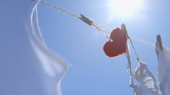 Single Red Paper Heart on a Clothesline - symbol for love Stock Footage
