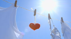 Single Red Paper Heart on a Clothesline - symbol for love - camera pan Stock Footage