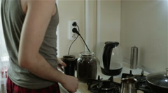 A young man putting coffee beans into a coffee mill Stock Footage