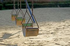 old chain swings in kids playground - stock photo