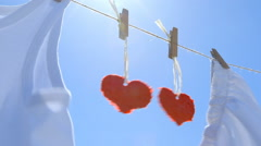 Two Paper Hearts on a Clothesline - symbol for love - stock footage