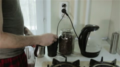 A young man putting ground coffee from a mill into a pot and pouring water Stock Footage