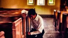 Man Kneeling In Church and Praying - stock footage