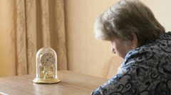Old woman looks at the table clock with pendulum Stock Footage