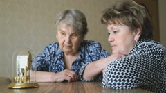 Two mature women looking at the table clock - stock footage