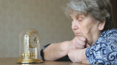 Old woman looks at the table clock with pendulum - stock footage