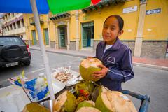 Cuenca, Ecuador - April 22, 2015: Young teenage girl working at coconut bicycle - stock photo
